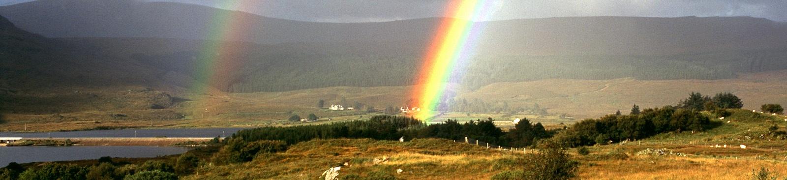 Double rainbows over a hillside