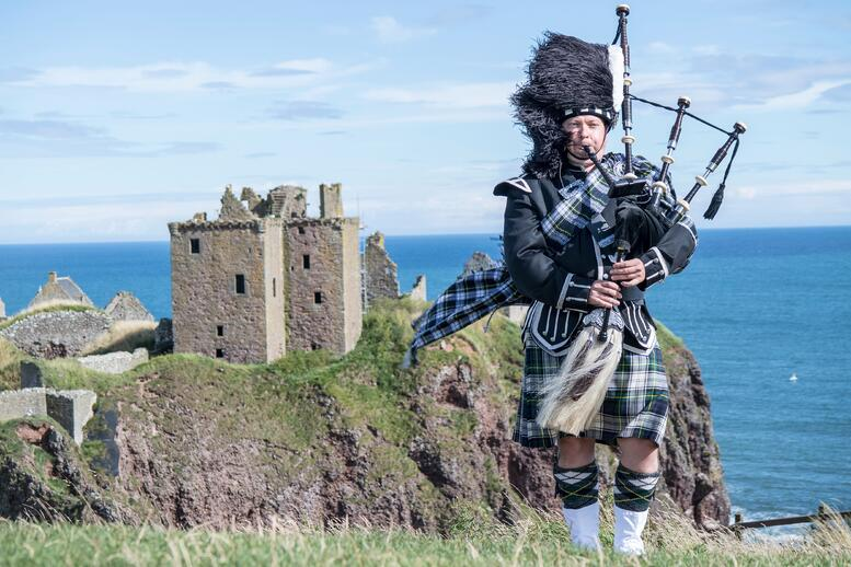 man playing bagpipes with castle in background
